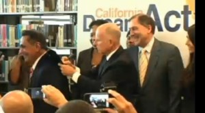 Gov. Brown signs Dream Act on back on its author, Assemblyman Gil Cedillo (photo from Assembly Access video)